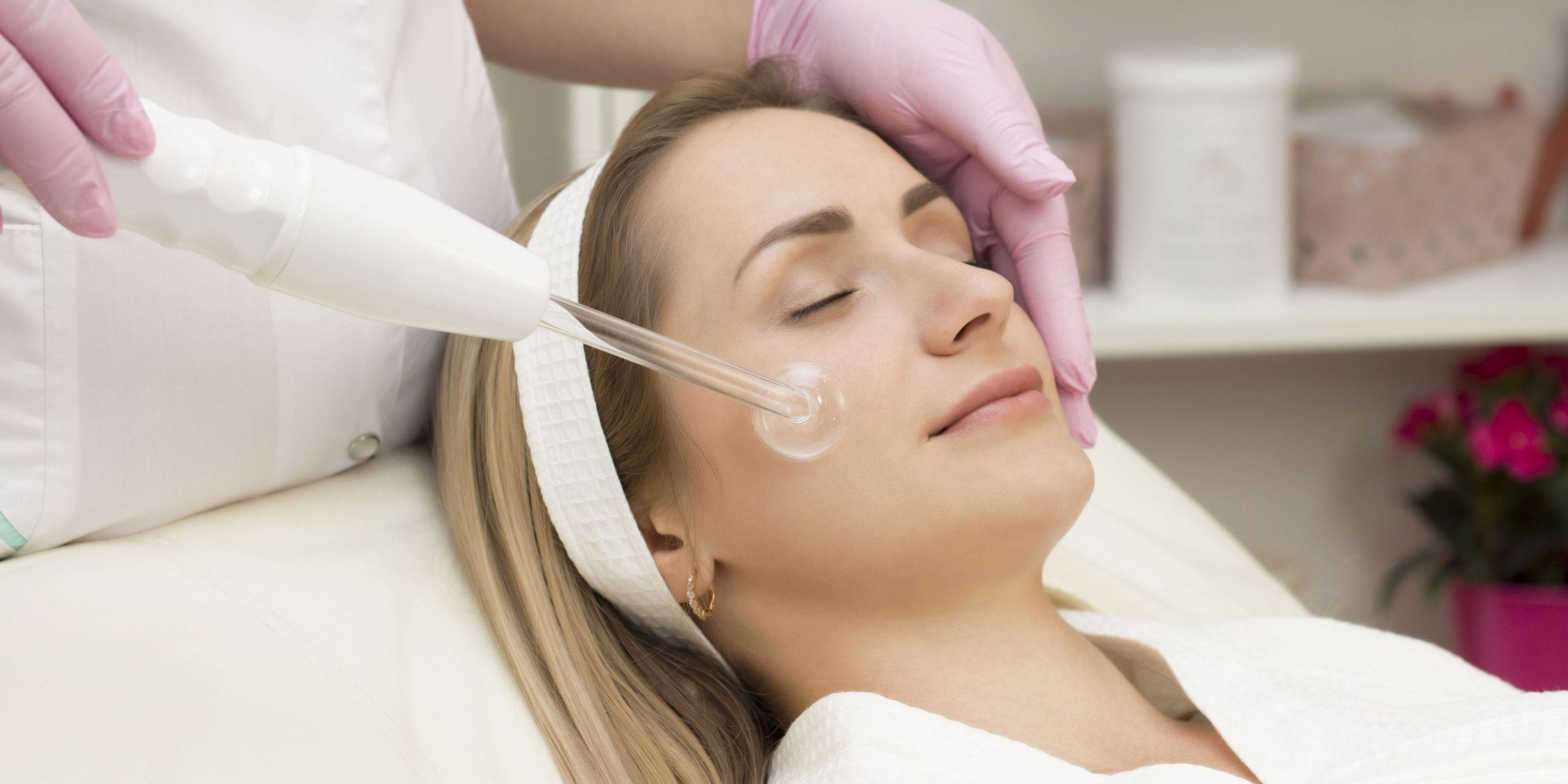Darsonvalization of the face or rejuvenation of the face with the help of electrotherapy. Photo of darsonval for the face. Current therapy. The patient is at the beautician